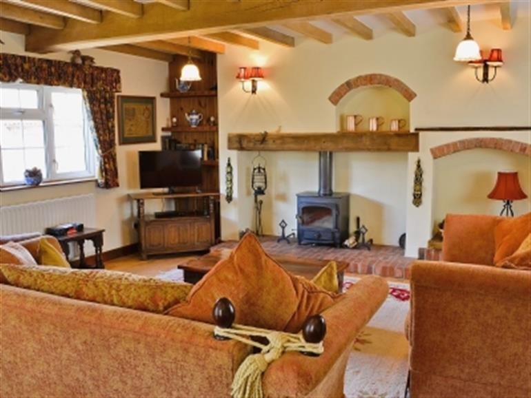 Living room with wood burner in St Giles Cottage, Ollerton near Newark
