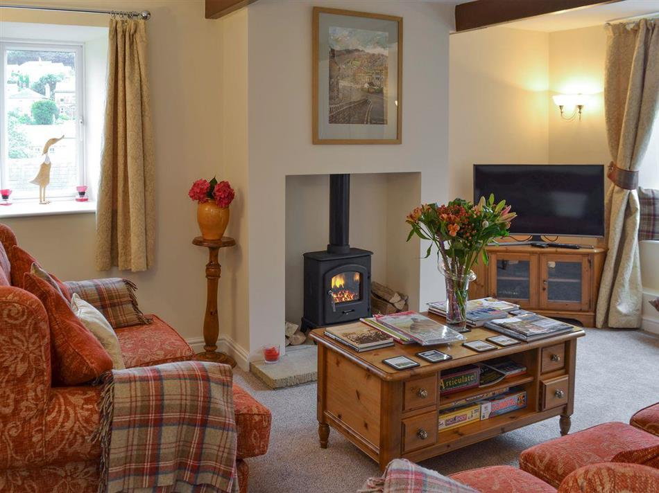 Living room with wood burning stove in Shelduck Cottage, Holmfirth