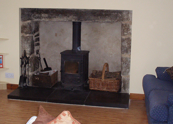 The living room at Pilmuir has a cost wood burning stove