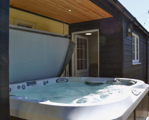 Enjoy the hot tub at Redmoor House - as well as the gym, sauna and indoor swimming pool