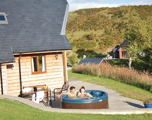 A private outdoor hot tub at one of the lodges at Slate House Lodges in Little London